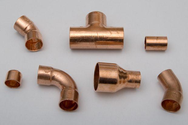 Kupferfittings (v.l.n.r.): Endkappe, Winkel 45° innen-innen, Bogen 90°, T-Stück, Reduzierstück, Muffe und Winkel 45° innen-außen.